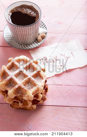 Thank you note and waffles - Cute thank you note on a piece of paper with a smiley face on it on a pink background near a hot cup of coffee and fresh waffles with powdered sugar.