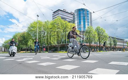 AMSTERDAM HOLLAND - AUGUST 19 2017; People cycle and motor cycle through city intersection with modern office buildings in background.
