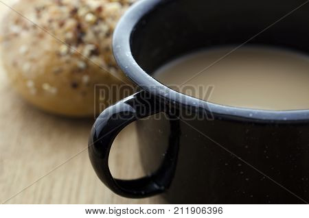 Close up photograph of a tin cup filled with coffee with cream. A roll covered in sesame and other seeds can be seen in the background.