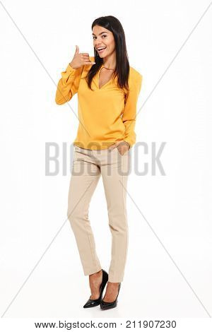 Full length portrait of cheerful brunette woman showing call me sign, standing with hand in her pocket, looking at camera, isolated on white background