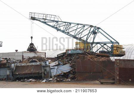 a working crane at a scrap heap will load iron