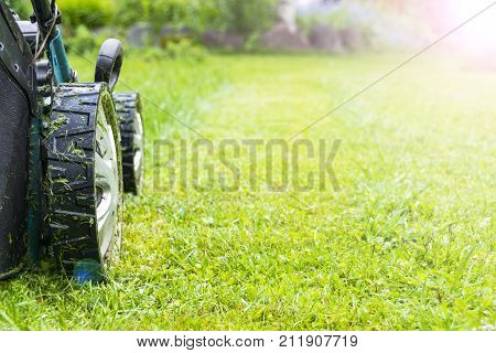 Mowing lawns Lawn mower on green grass mower grass equipment mowing gardener care work tool close up view sunny day. Soft lighting