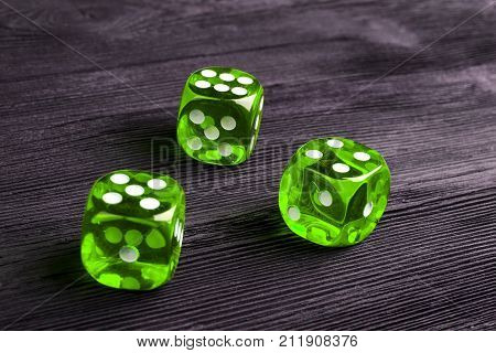 risk concept - playing dice at black wooden background. Playing a game with dice. Green casino dice rolls. Rolling the dice concept for business risk chance good luck or gambling