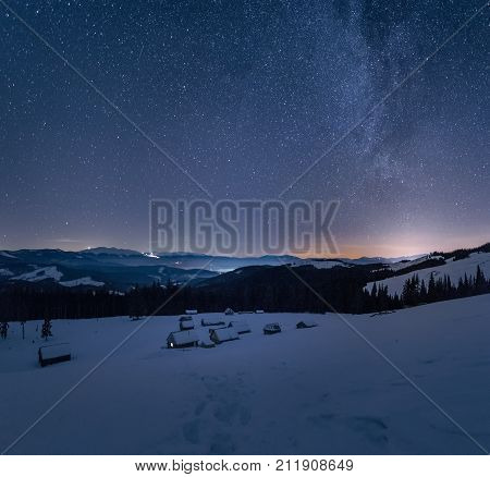 Winter Landscape Of A Mountain Range At Night. Stars Over The Mountain Range. Snow Covers Slopes Of