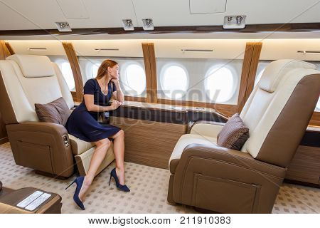 young beautiful woman in Luxury interior in bright colors of genuine leather in the business jet sky and clouds through the porthole