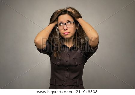 Young tired business woman looking upward and holding her head with her hands. Student girl trying to solve her problem. No exit situation. Tired of work concept.
