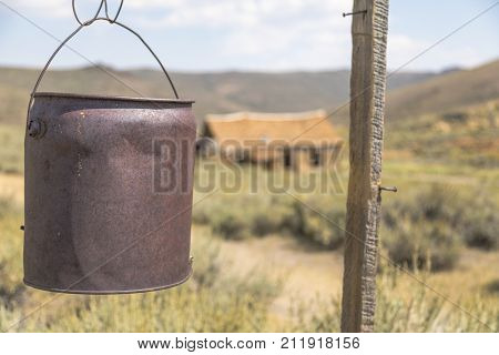 BODIE, CALIFORNIA, USA - August 31, 2017 : Old well bucket and buildings in Bodie ghost town, California. Bodie is a historic state park from a gold rush era in the Bodie Hills east of the Sierra Nevada
