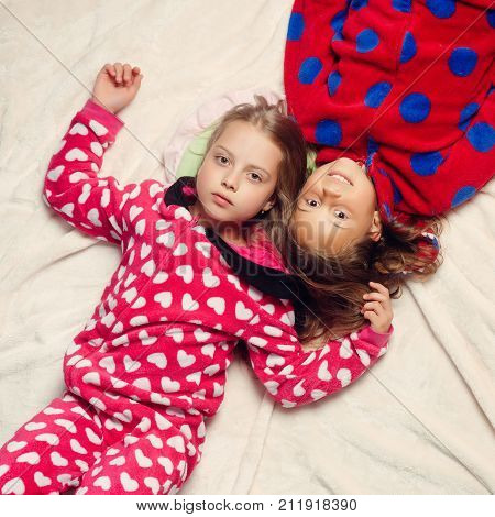 Girl sisters in pajamas lie in bed top view. Comfort home concept. Children nightwear fashion. Bedtime slumber dream sleepover. Childhood family love friendship.