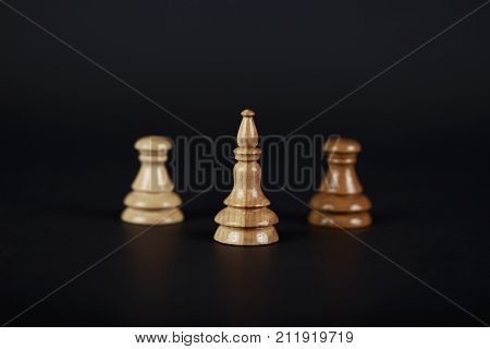 Wooden chess figure of an elephant on a black background with two pawn different color. An elephant is a traitor. The chess figure did not decide which side it was on.