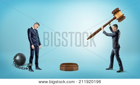 A small businessman strikes a gavel on a sound block near a sad ankle chained businessman. Business and competition. Corporate law. Colleagues and enemies.