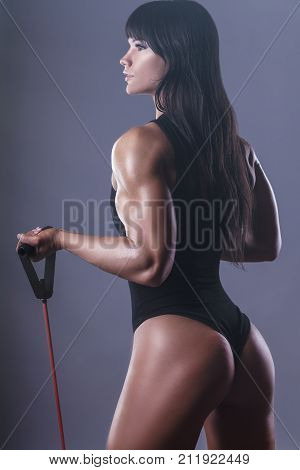 Sport concept. Athletic young woman exercising with rubber band against a dark background. Back view