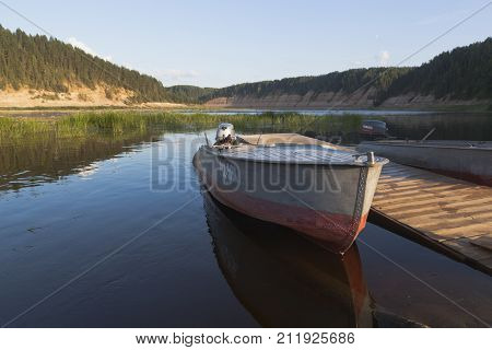 Opoki, Velikoustyugsky district, Vologda region, Russia - August 12, 2016: Boats in the summer evening at a wooden pier on the Sukhona River in the tract of Opoki