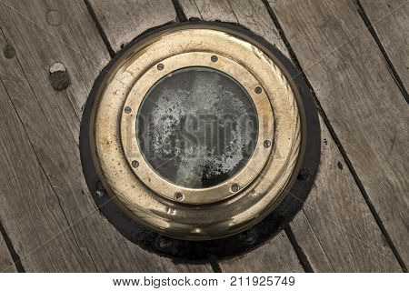 Porthole Of A Sailing Ship With A Wooden Surround