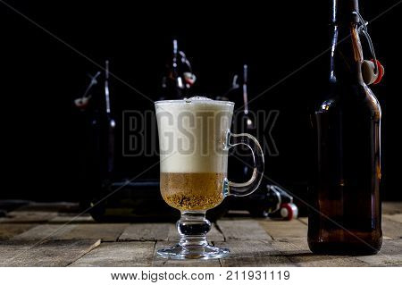 A Pint Of Tasty Beer On A Wooden Table. Beer In Pint And Beer Bottles.