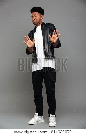 Full length photo of young displeased african guy swoving stop gesture, looking at camera, isolated on gray background