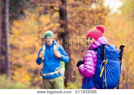 Couple hikers camping in beautiful yellow autumn forest and mountains. Young partnership teamwork man and woman walking with backpacks healthy lifestyle adventure camping on hiking trip.