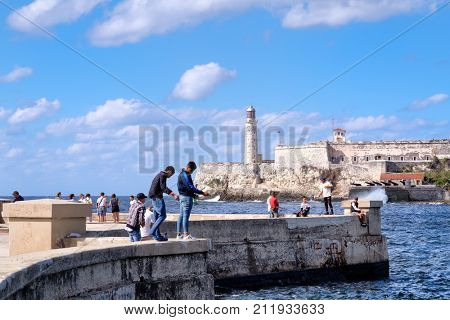 HAVANA,CUBA - OCTOBER 7, 2017 : People fishing at the malecon seawall in Havana with El Morro fortress on the background