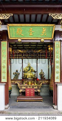 Shanghai, China - Nov 6, 2016: In the 600-year-old Old City God Temple. Statue of the legendary General Guan Yu (patron Taoist deity) in glass cabinet. Altar at front.