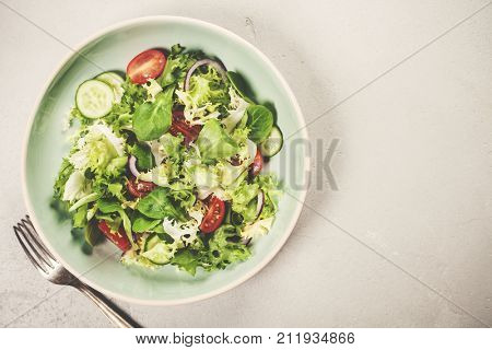 Salad. Vegetable salad. Spring vegetable salad. Fresh vegetable salad with tomatoes onion cucumber and olive oil.Top view