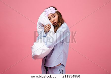 Portrait of a tired pretty girl dressed in pajamas holding pillow and sleeping while standing isolated over pink background