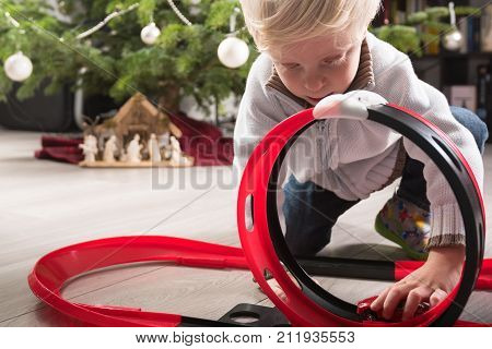 Boy playing with his Christmas present, a plastic racetrack in front of the Christmas tree
