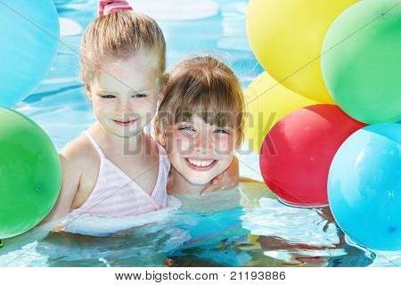 little girl playing with balloons in swimming pool.