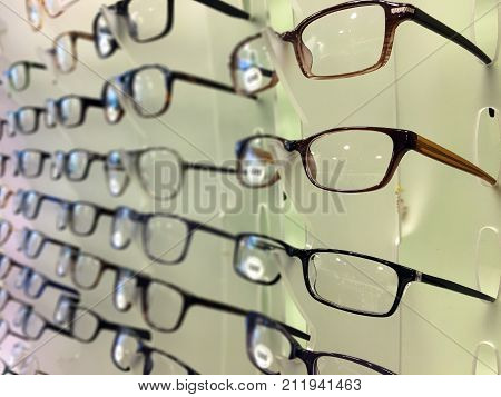 Close up of eyeglasses at optician store on a rack of eyeglasses shop. Optics health care and vision concept.