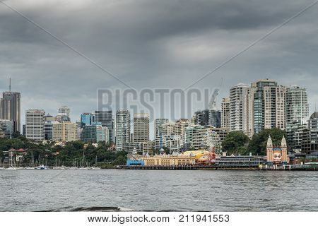 Sydney Australia - March 22 2017: Colorful Luna Park attractions on shore with towers of Kirribilli business district in the back. All under heavy dark cloudscape.