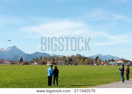 Schongau, Germany - October 31, 2017: Asian people are playing with RC quadrocopter toy aka drone in front of the Bavarian Alps.