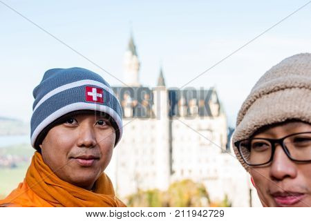 Schwangau, Germany - October 31, 2017: Buddhist monks are visiting the world-famous Neuschwanstein Castle, the 19th century Romanesque Revival palace built for King Ludwig II, with scenic mountain landscape in southwest Bavaria, Germany.