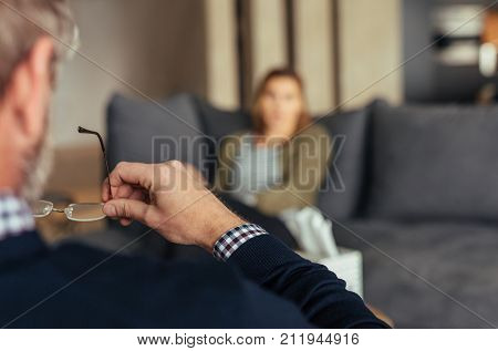 Hands of psychologist holding glasses and listening to woman in trouble during therapy session. Psychotherapist understanding problems of a woman patient.