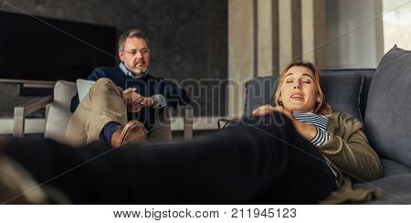 Depressed woman lying on couch during psychotherapy session. Female patient discussing her issues with psychologist during therapy.