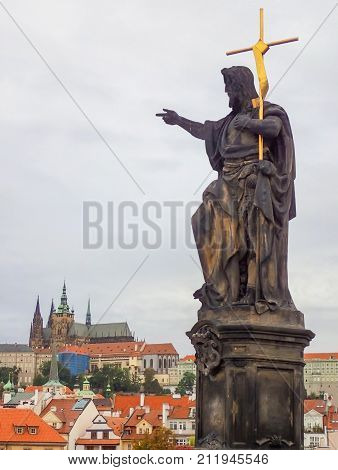 Statue on St. Charles Bridge with Cross Points to Cityscape and Castle