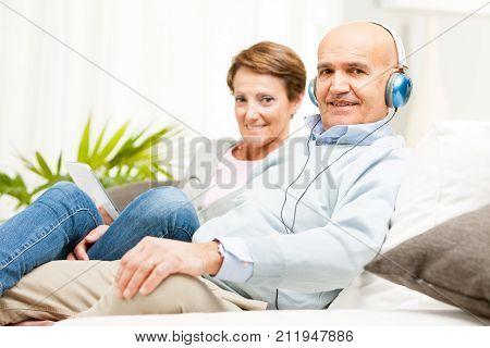 Mature affectionate couple relaxing together on a sofa at home listening to music on headphones