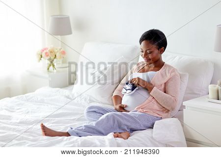 pregnancy, people and rest concept - happy pregnant african american woman with baby bootees in bed at home bedroom