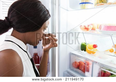 Close-up Of An African Young Woman Holding Her Nose Near Foul Food In Refrigerator