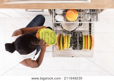 Smiling Young African Woman Arranging Plates In Dishwasher