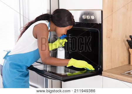 Young African Woman Wearing Yellow Gloves Cleaning Oven With Spray Bottle And Sponge