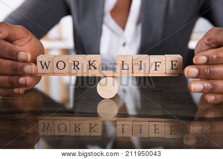Close-up Of A Businesswoman's Hand Covering Balance Between Life And Work On Seesaw