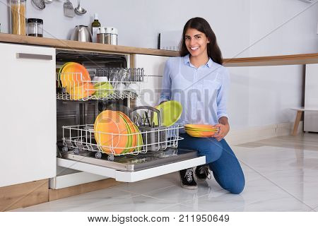 Young Woman Arranging Plates In Dishwasher At Home
