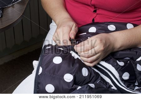 Sewing Clothes By An Individual Entrepreneur. The Woman Is Working Scissors. Unravels The Seam Of Th