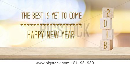 Wooden cubes with 2018 and the best is yet to come happy new year over blur bokeh background banner positive quotation new year greeting card