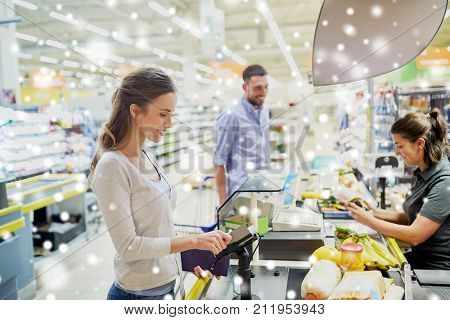 shopping, sale, consumerism and people concept - happy couple buying food at grocery store or supermarket cash register and swiping customer card over snow