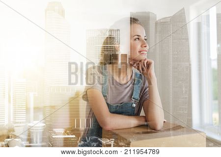 mortgage, people and real estate concept - happy woman with box moving to new home over city buildings background and double exposure effect