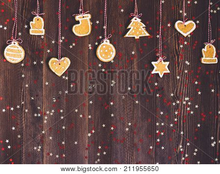 Gingerbread cookies on rope for christmas tree decoration new year on wooden table. Festive sweet pastry delicious food. Various cookies gingerbread star heart christmas ball sock Santa Claus mitten