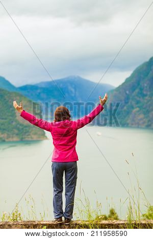 Woman With Raised Hands In Norwegian Mountains Fjords