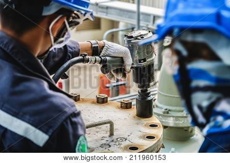 Workers hand holding machine tightening nut The mechanic is repairing the machine in the factory Maintenance team in industrial plant