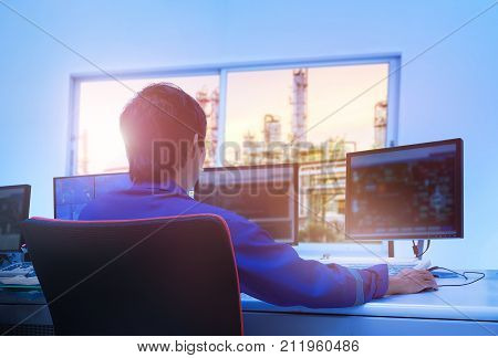 Professional technician sitting in control room monitoring process petrochemical plant Asian broad man operate process plant Engineers work