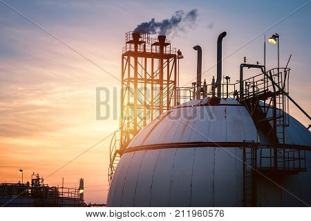 Petrochemical industrial on sky sunset background Factory with evening time Gas sphere tank and storage tank in oil refinery plant on sky sunset