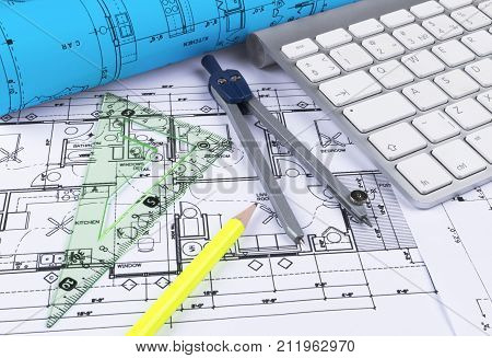 Architectural blueprints drawings of the modern house with computer keyboard. Architectural blueprints and blueprint rolls and a drawing instruments on the worktable. Drawing compass plans.